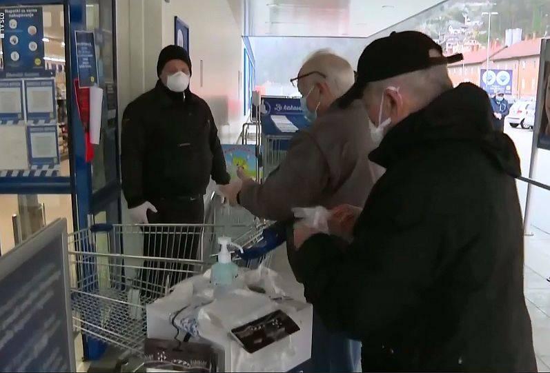 Varnostnik pred trgovino nadzira zaščitno opremo obiskovalcev. Foto: Televizija Slovenija